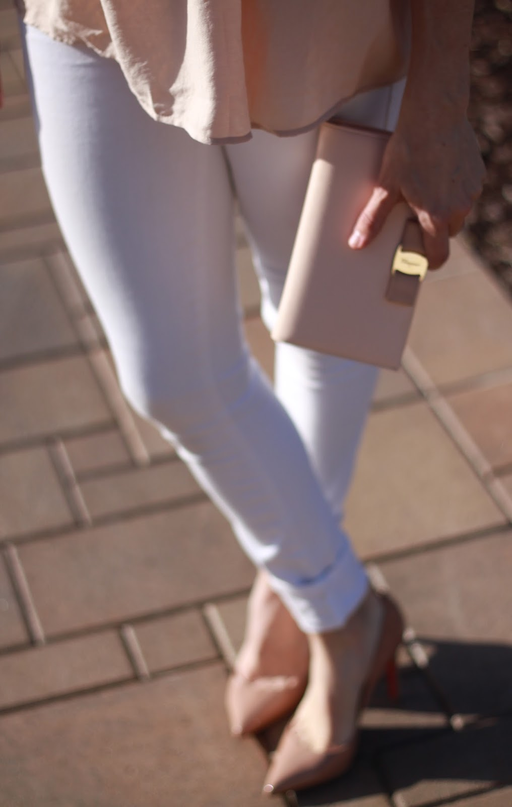 blush clutch and white skinny jeans