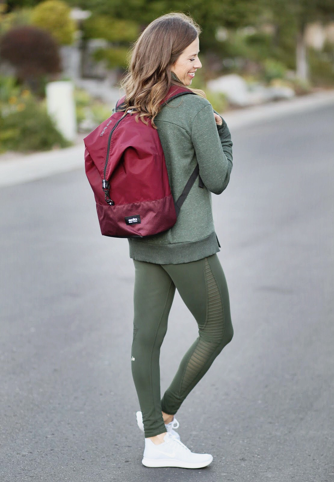 burgundy back pack and moto leggings